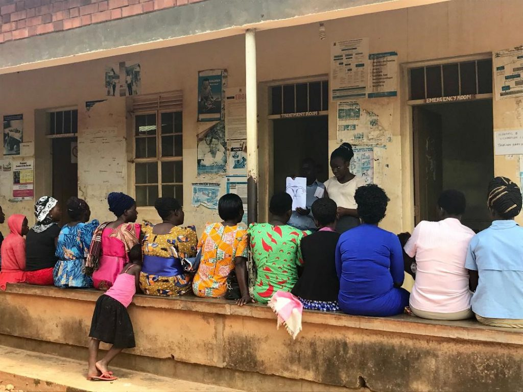 Photo from a health center in Busoga Region, women sitting in front of health center
